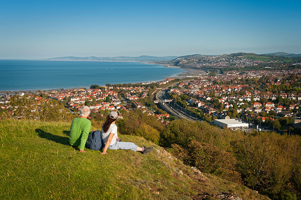 Female and male walkers near summit of Bryn Euryn hill looking over Colwyn Bay towards Clwydian Range Rhos-on-Sea Conwy County North Walking Activities and Sports